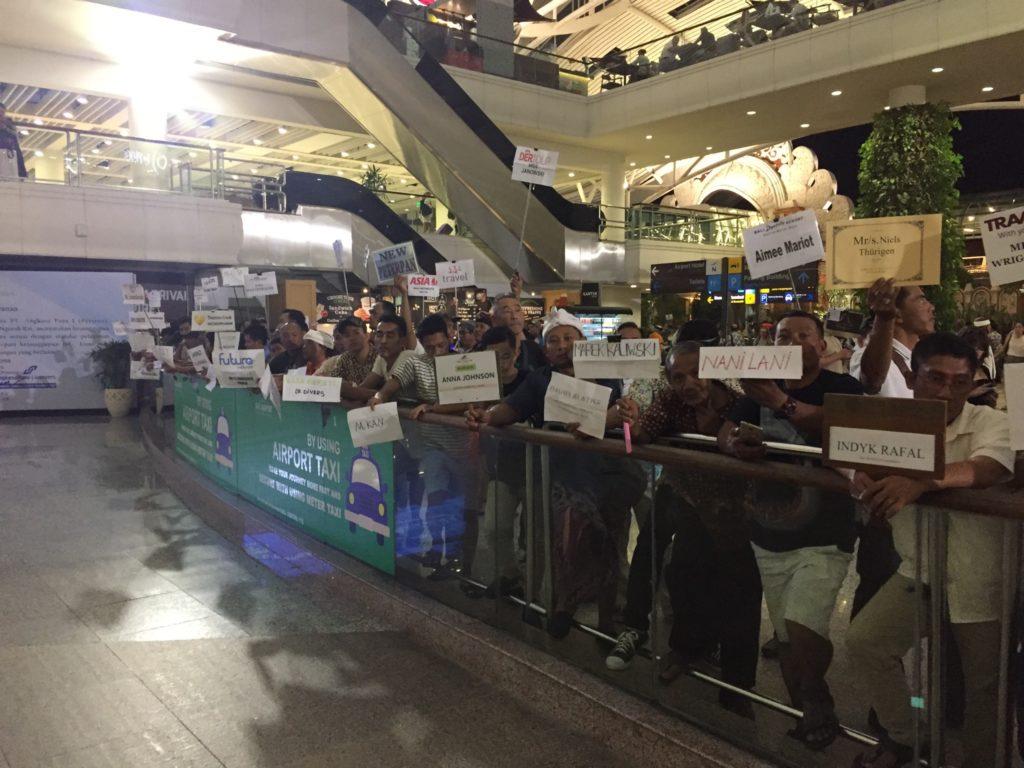sortie de l'aéroport de Bali avec des dizaines de chauffeurs portant tous une pancarte avec la direction d'Ubud