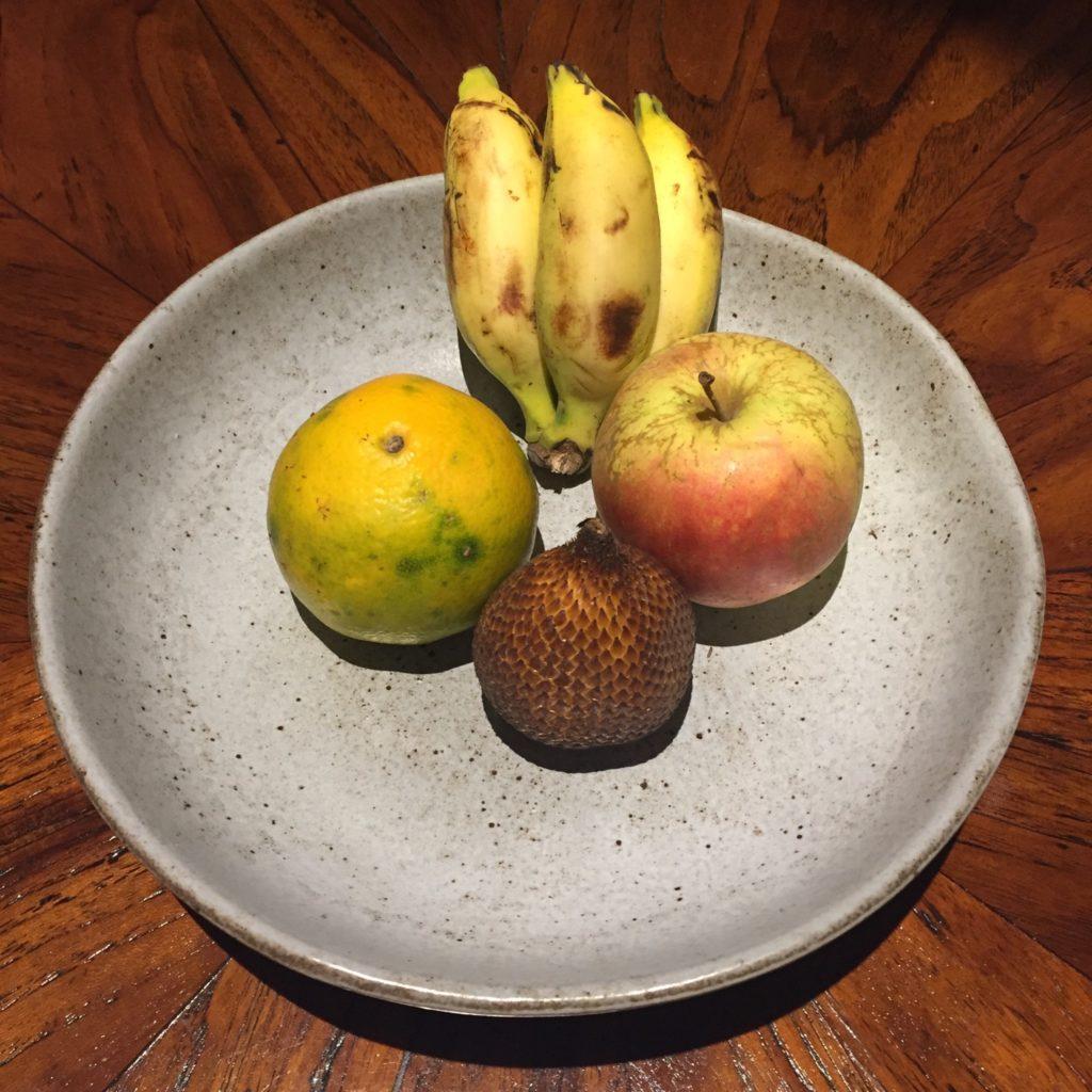 plateau de fruit avec une orange, une pomme, 3 mini bananes et un fruit inconnu